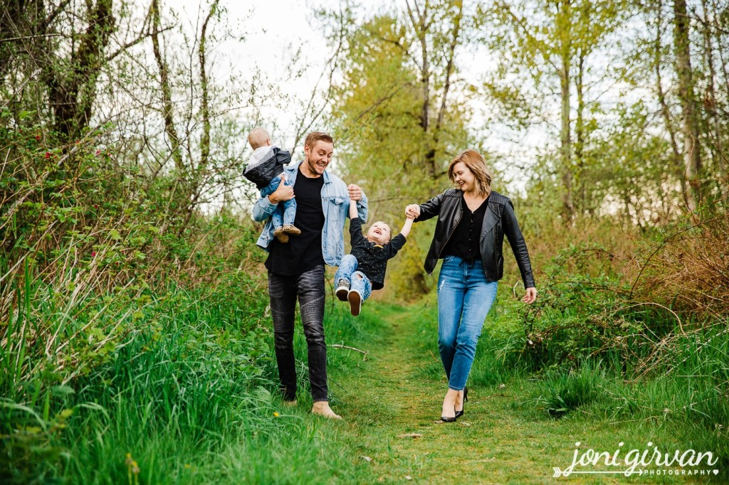 Young family wearing black and denim outfits. Parents swinging young child between them and smiling.